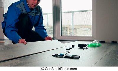 Worker in blue work wear laid wood floor in white room.