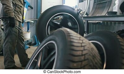 Worker in car service repairs tires - mechanical workshop,...
