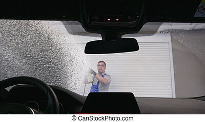Worker in car washing shop throwing soap on car window. View from inside the car.