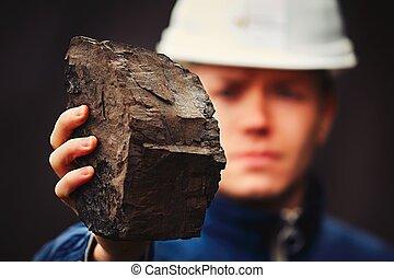 Worker in coal mine - Worker is showing lignite - often...