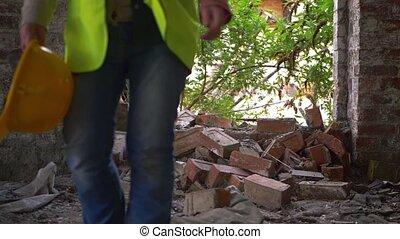 Worker in demolished building with hard hat medium slow motion shot