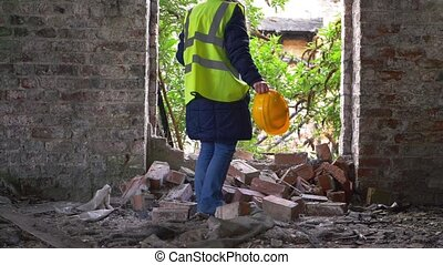 Worker in demolished building with hard hat wide slow motion shot