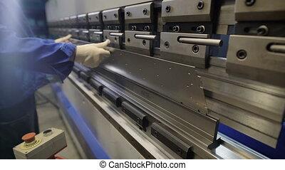 Worker in factory at metal skip machine putting work piece...