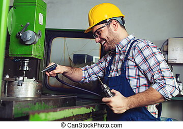 Worker in factory using drill machine