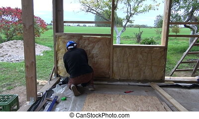worker in farm insulating with rockwool wall construction -...
