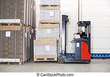 Worker In Forklift Examining Stockpile