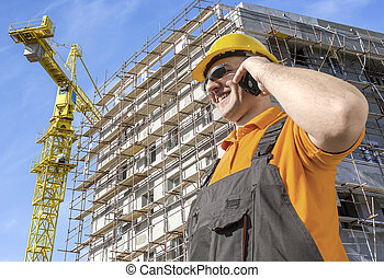 worker in front of construction site talking on smart phone