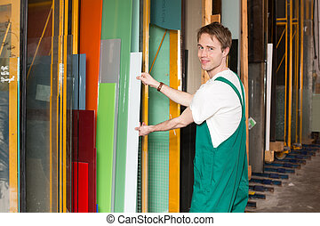 Worker in glass glazier's workshop