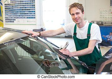 Worker in glazier's workshop installs windshield - Glazier ...