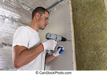 Worker in goggles with screwdriver working on insulation. Drywall on wall beams, insulating rock wool staff in wooden frame. Comfortable warm home, economy, construction and renovation concept.
