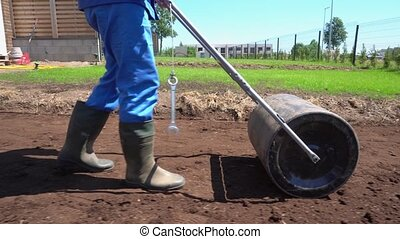 Worker in gumboots working with soil earth roller. Stabilizer Gimbal parallel movement follow shot
