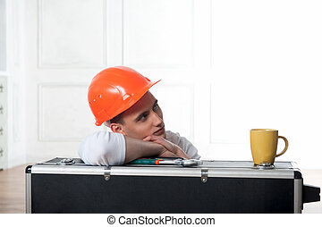 Worker in helmet with coffee cup