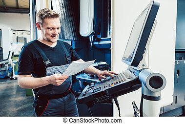 Worker in industrial workshop programming a cnc machine
