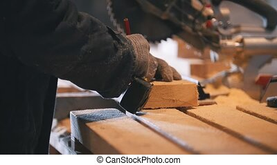 Worker in joinery figuring wooden board before circular saw ...