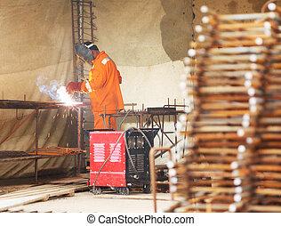 Worker in orange clothes weld metal gratings by acetylene torch