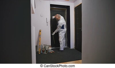 Worker in overalls, takes measurements of the doorway, he was a professional builder.