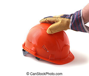 worker in protective gloves holds an orange hard hat in his hand. Safety helmet.