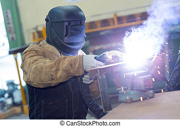 worker in protective mask using gas torch making large flame