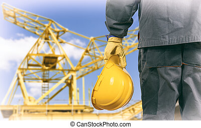 worker in protective uniform and protective helmet in front of construction crane