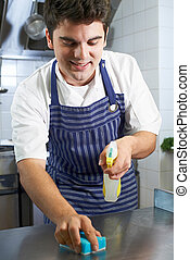 Worker In Restaurant Kitchen Cleaning Down After Service