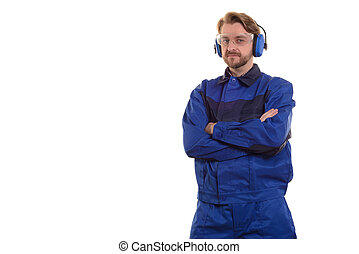 worker in safety glasses and headphones stands with his arms crossed over his chest