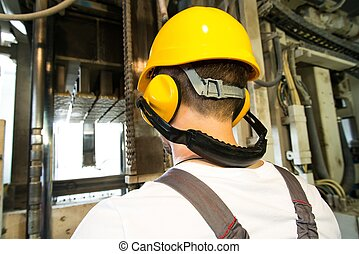 Worker in safety hat and headphones working behind machine...