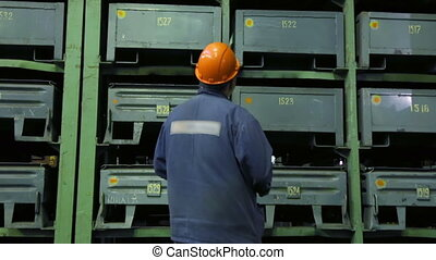 Worker in storage shop at machine works