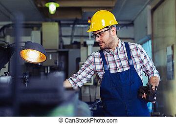 Worker in uniform operating in manual lathe in metal industry factory
