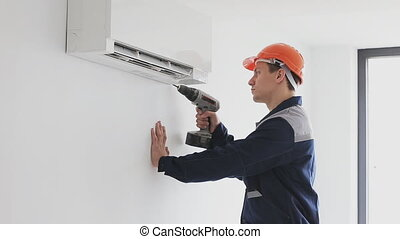 Worker in uniform sets air conditioning - air conditioning...