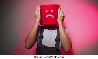 Worker in uniform with red bucket on his head sad.