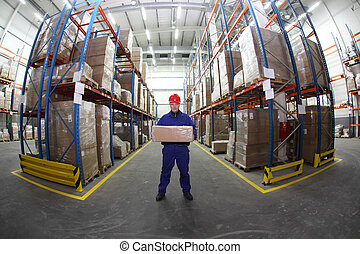 worker in warehouse - worker in blue uniform with box in the...
