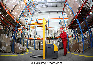 worker in warehouse - worker in red uniform at work in...