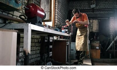 Worker in workshop processing metal details, wide angle