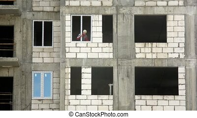 Worker inserts frames and glass in window of the building....