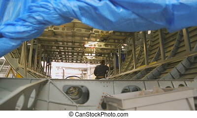 Worker inside fuselage mounts to luggage compartment. Worker in blue uniform holding in his hand a paper document and compares it with work performed. All done and finished works have multiple layers of validation. Housing consists of longerons and stringers and plating they are made of aluminum. ...
