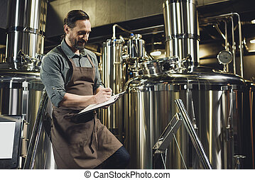 Worker inspecting equipment at brewery - Male worker in...