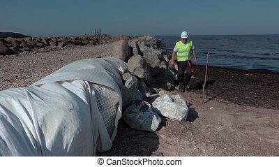 Worker inspecting stone isolation at piers