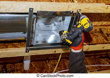Worker installing air conditioner vents in new home construction