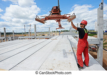 worker installing concrete slab - worker in safety...