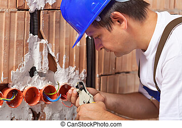 Worker installing electrical wires in building wall - Worker...