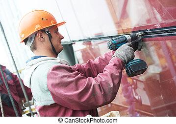 worker installing glass window on building