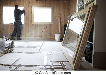 Worker installing new wooden windows