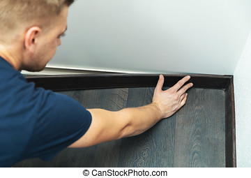 worker installing plastic baseboard on the laminate floor
