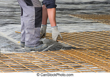 Worker installing reinforcement mesh - Construction worker...