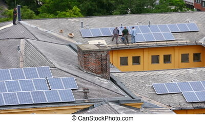 worker installing solar panel roof top apartment