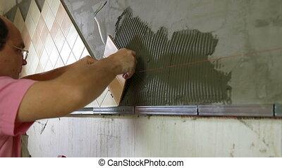 Worker installing Tile