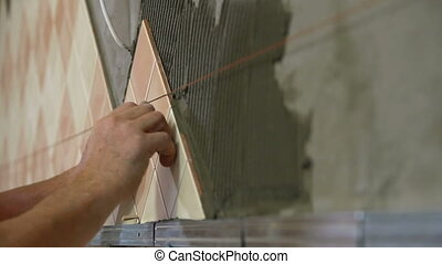 Worker installing Tiles - man applying ceramic tile to a...