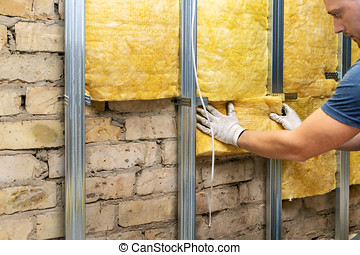 worker insulating old brick wall with glass wool sheets