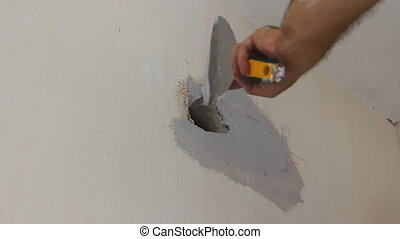 Worker is applying skim coating material around wall socket...