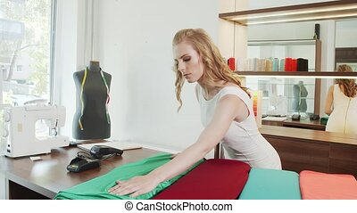Worker is arranging rolls of a fabrics in a textile store...